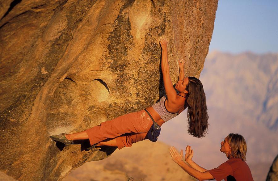 Action Photograph - A Man Spots A Female Rock Climber On An by Corey Rich