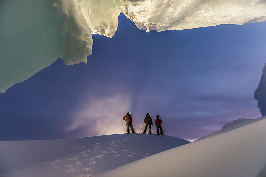 Adult Photograph - A Man Stands At The Entrance Of An Ice by Alasdair Turner