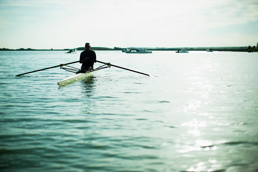 A Mature Man In A Rowing Boat On The Photograph by Mint Images/ Jamie Kripke