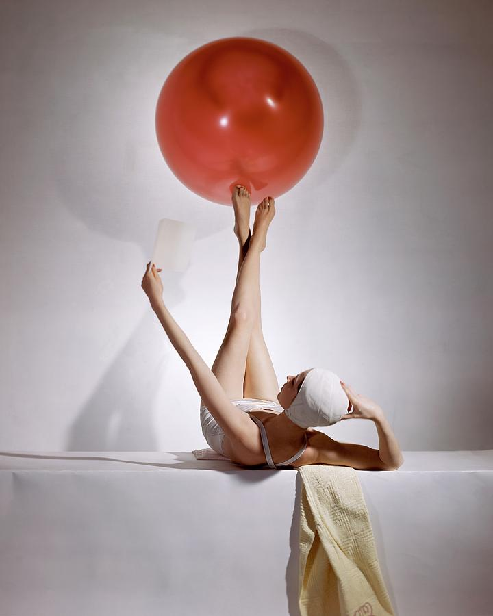 A Model Balancing A Red Ball On Her Feet Photograph by Horst P Horst