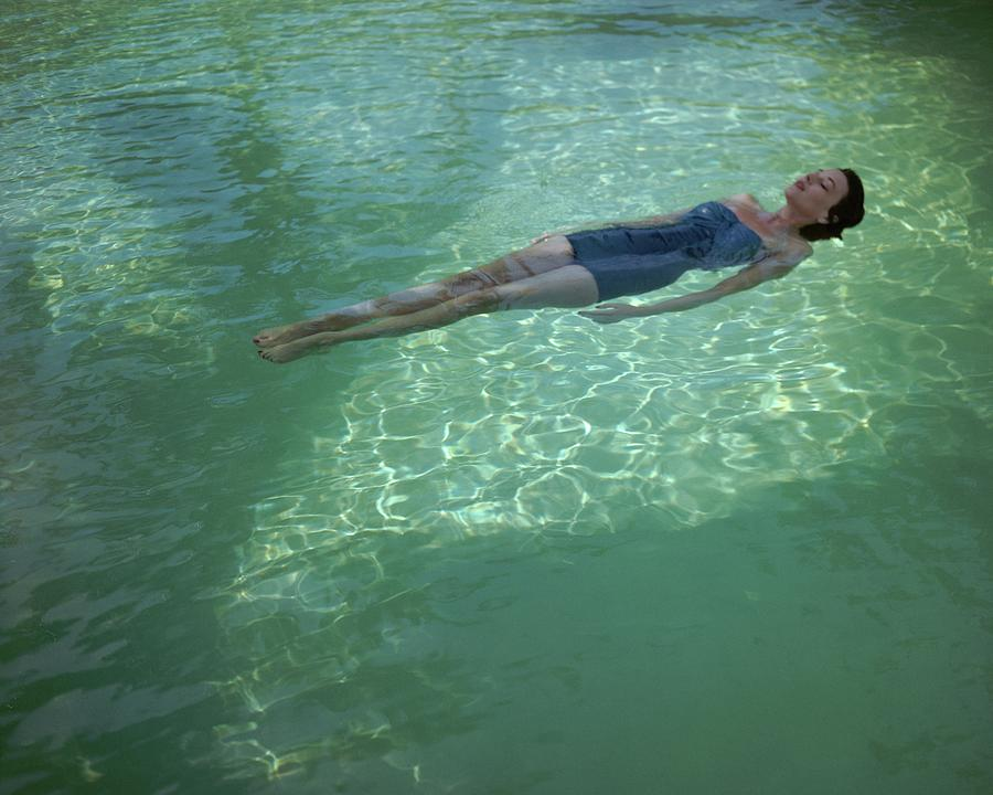 A Model Floating In A Swimming Pool Photograph by John Rawlings