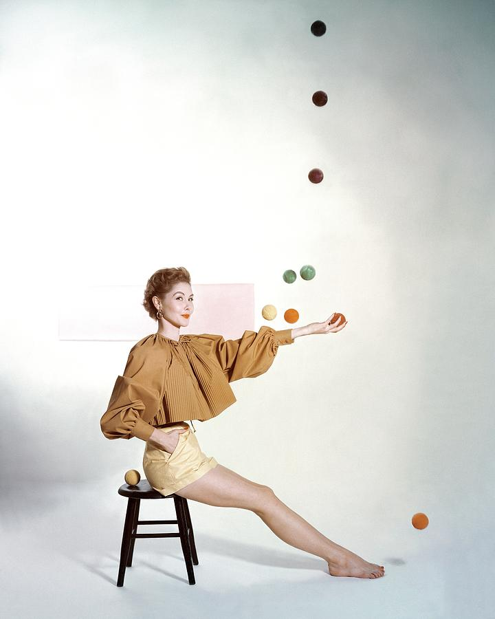 A Model Sitting On A Stool Juggling Photograph by John Rawlings