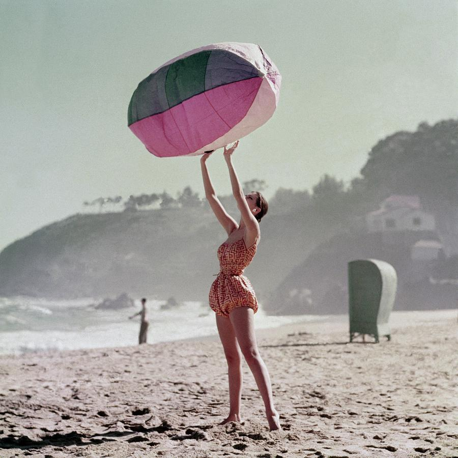 A Model Wearing A Bathing Suit Holding Up An Photograph by Richard Rutledge
