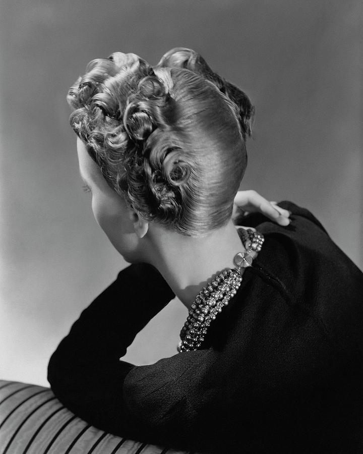 A Model Wearing A Curled Hairstyle Photograph by John Rawlings