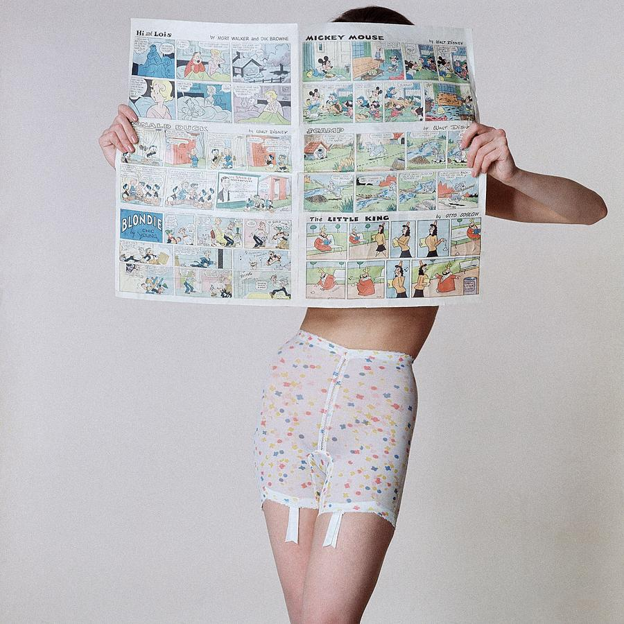 A Model Wearing A Girdle With A Comic Photograph by Louis Faurer