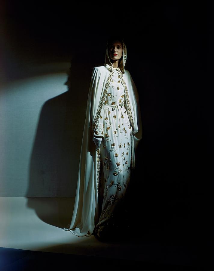 A Model Wearing A Hooded Ivory Cape Over An Ivory Photograph by Horst P. Horst