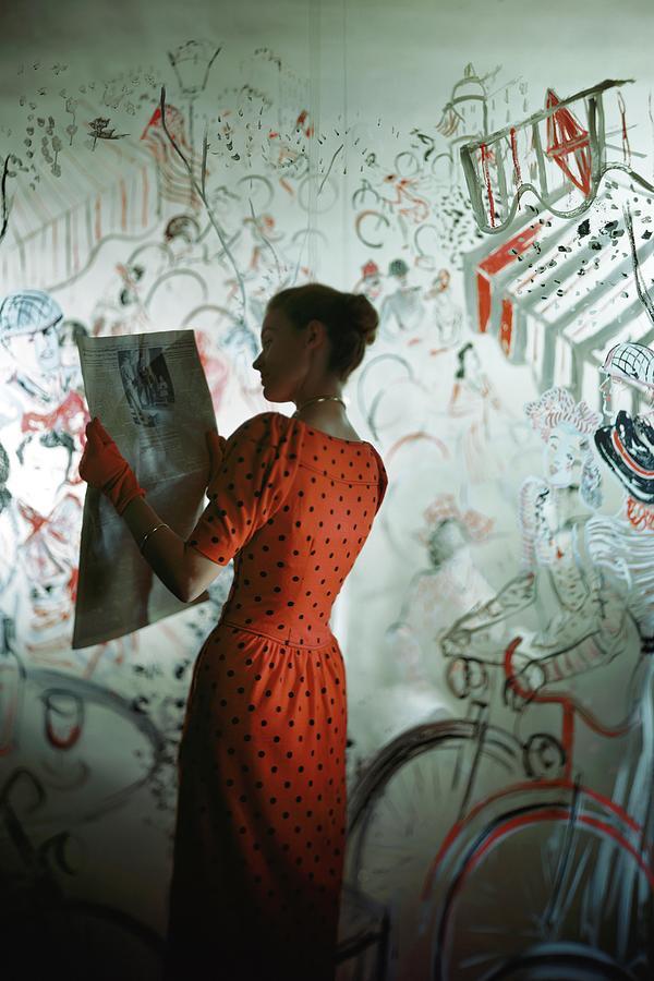 A Model Wearing A Polka Dot Dress Reading Photograph by Constantin Joffe