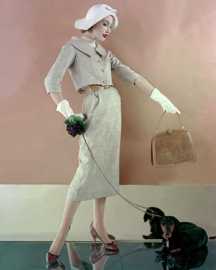 A Model Wearing A Tweed Jacket And Skirt Photograph by Karen Radkai