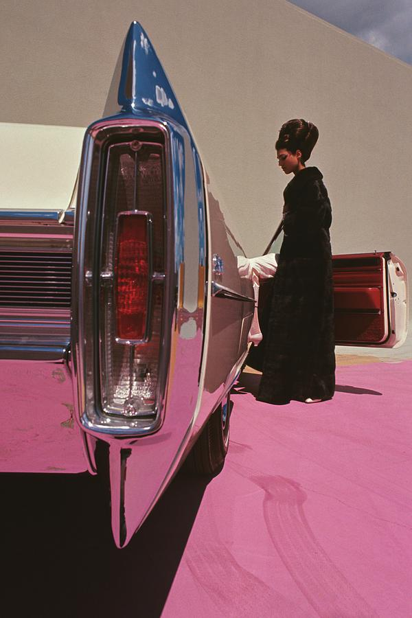 A Model Wearing Emeric Partos Entering A 1965 Photograph by Gene Laurents