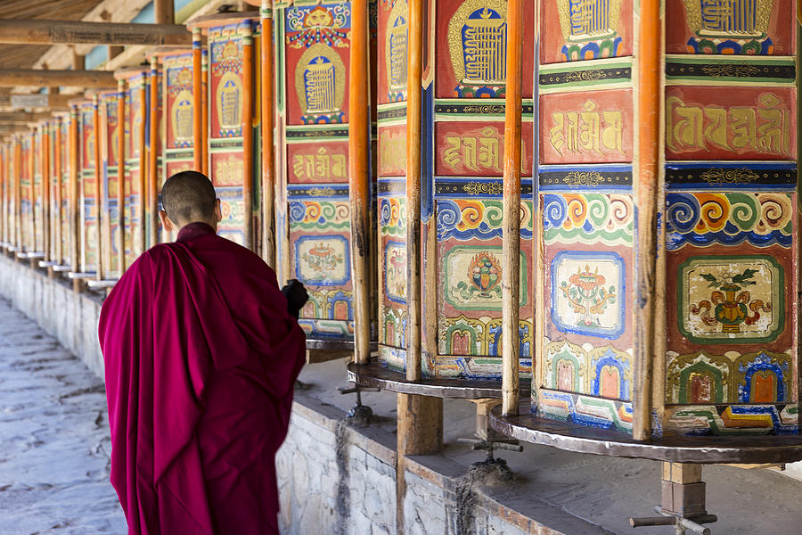A monk is walking and turning huge and colorful prayer wheels in Labrang Monastery Photograph by Aiqingwang