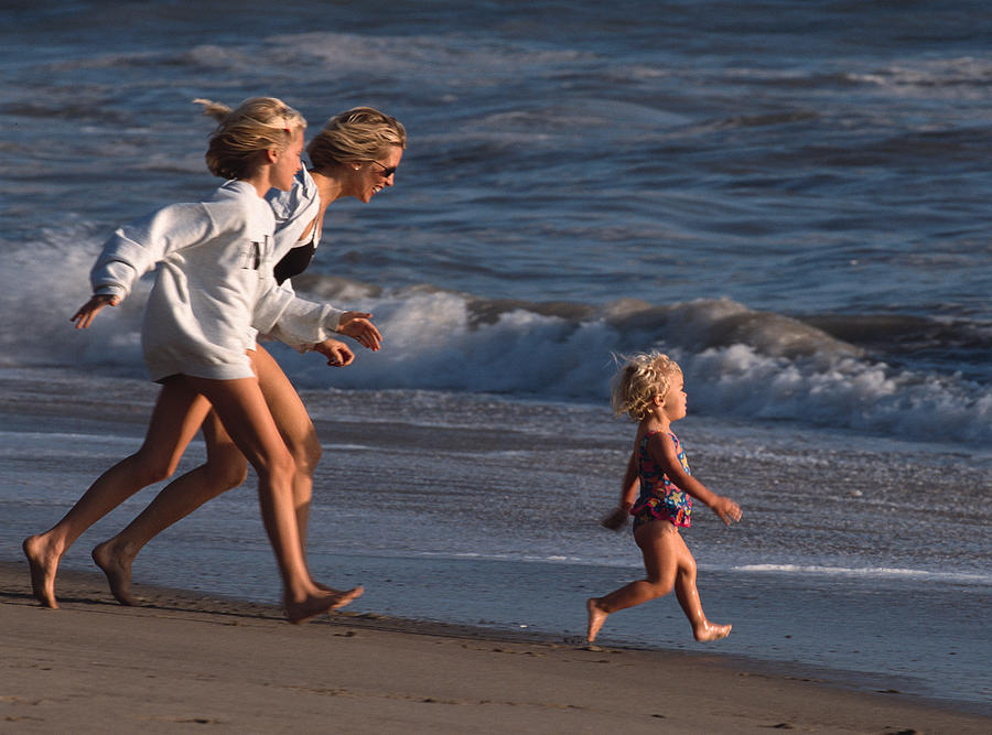 A Mother And Teenage Daughter Run After A Toddler On The Beach Photograph by Photodisc