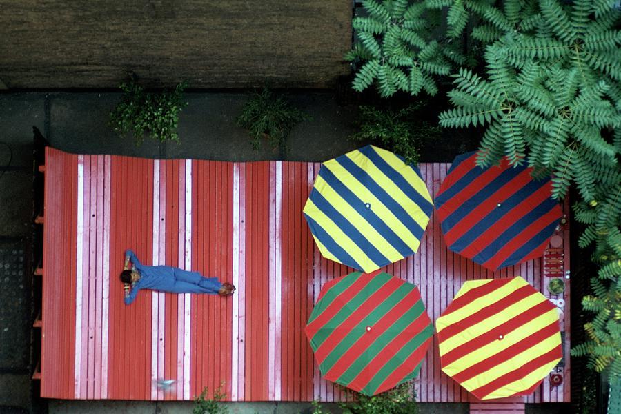 A Patio With Striped Umbrellas Photograph by James Mathews