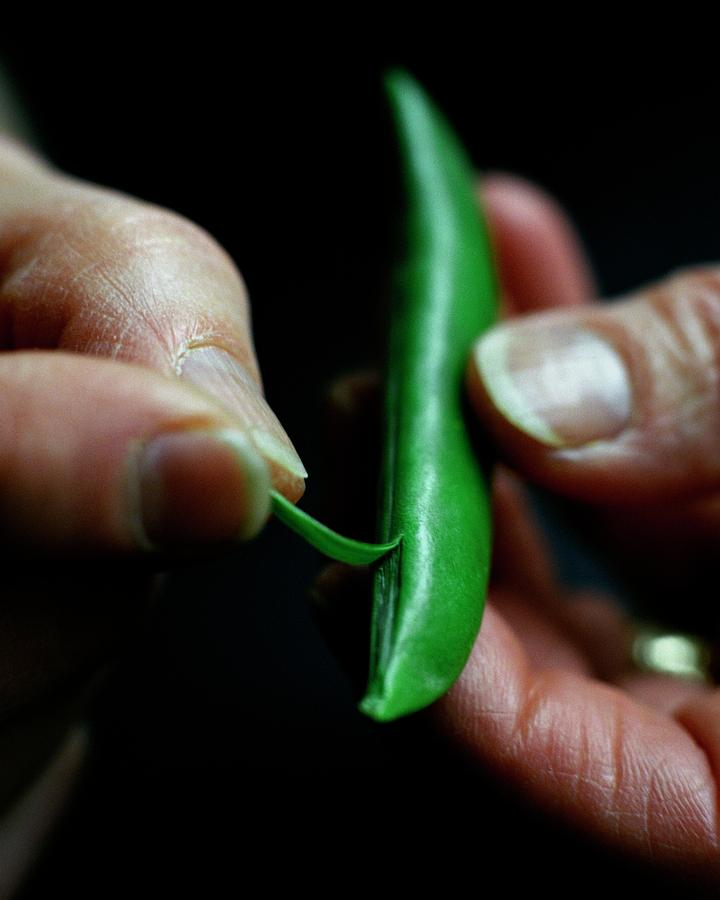 A Person Peeling A Bean Photograph by Romulo Yanes