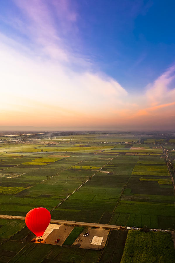 Adventure Travel Photograph - A Red Hot Air Balloon Landing In Egyptian Fields by Mark E Tisdale