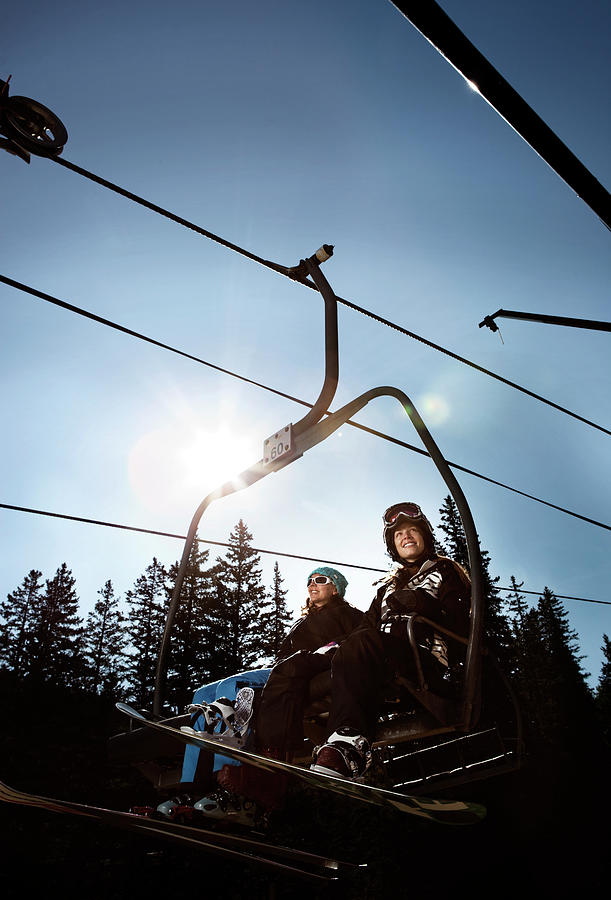 20s Photograph - A Skier And Snowboarder Share The Chair by Ryan Heffernan