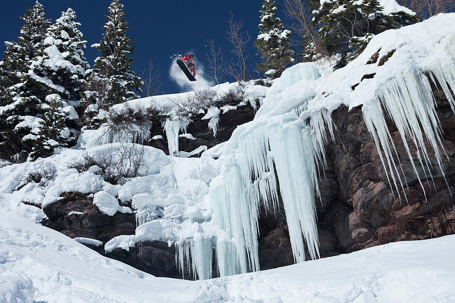 Action Photograph - A Snowboarder Jumps Off An Ice by Patrick Orton