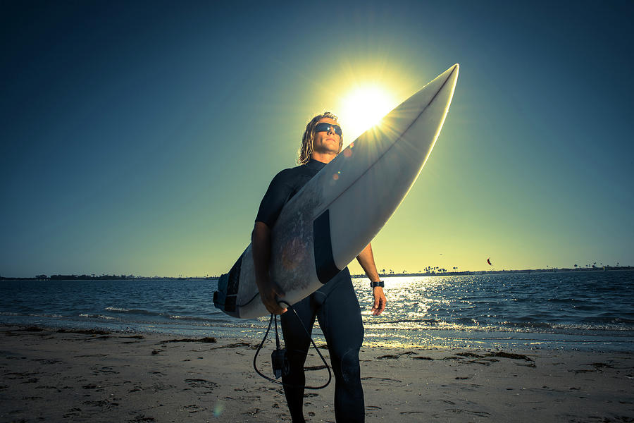 Adult Photograph - A Surfer Walks Down The Beach by Rob Hammer