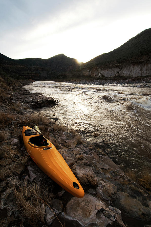 Absence Photograph - A Whitewater Kayak Rests On The Shore by Kyle George