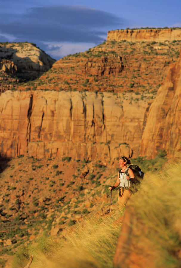 Backpack Photograph - A Woman Hikes Along The Base Of A Wall by Rich Wheater