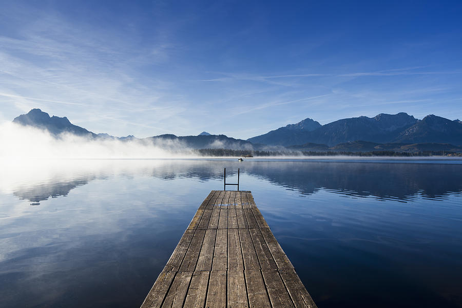 A wooden jetty on Lake Hopfensee at sunrise Photograph by Jorg Greuel