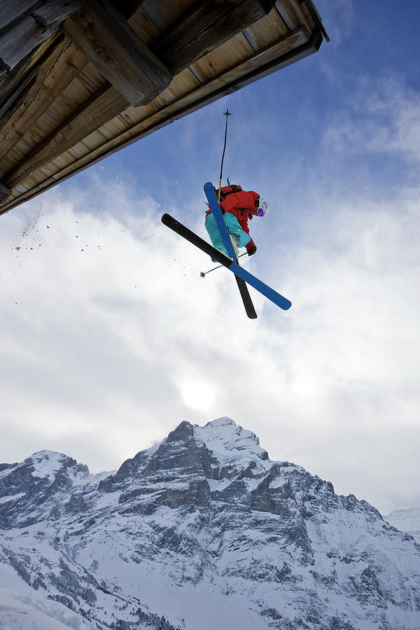 Adventure Photograph - A Young Man Skis Off The Roof Of An by Henry Georgi
