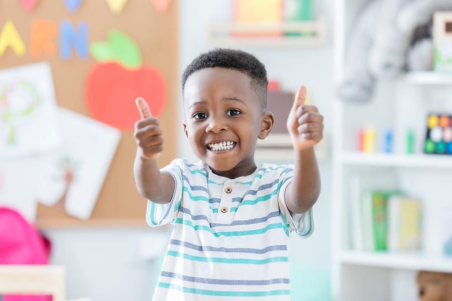 Adorable boy gives thumbs up in preschool Photograph by Asiseeit