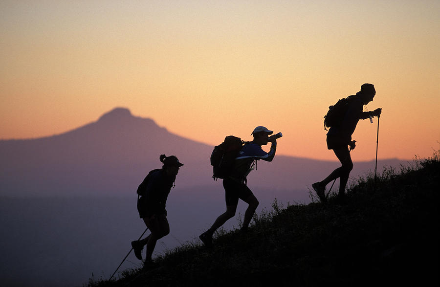 Action Photograph - Adventure Racing Team Hiking At Sunset by Corey Rich