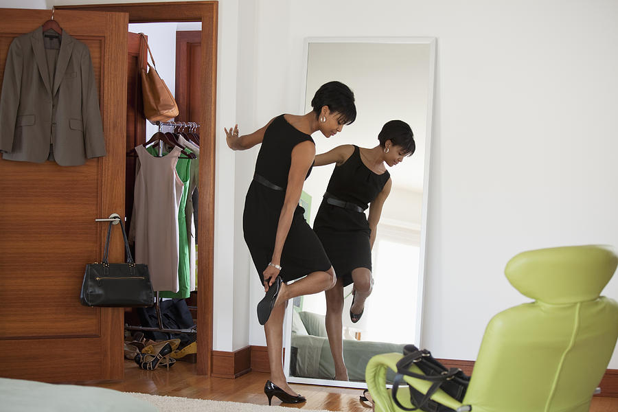 African American Woman Dressing In Bedroom Photograph by Ariel Skelley
