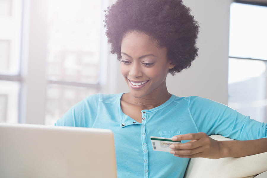 African American woman shopping on laptop with credit card on sofa Photograph by Jose Luis Pelaez Inc