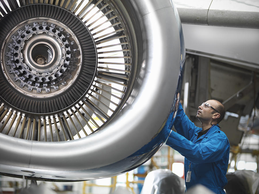 Aircraft engineer working on 737 jet engine in airport Photograph by Monty Rakusen