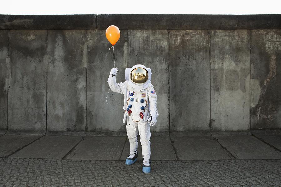 An astronaut on a city sidewalk holding a balloon Photograph by fStop Images - Caspar Benson