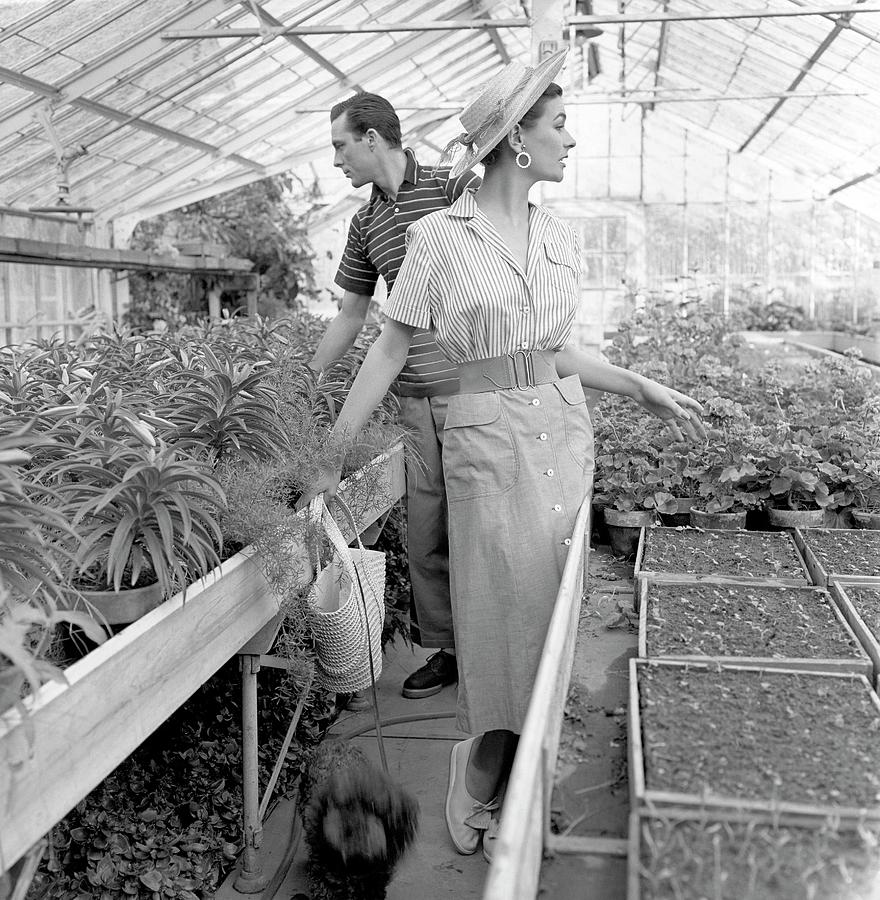 Anne Gunning Parker With A Man In A Greenhouse Photograph by Horst P. Horst