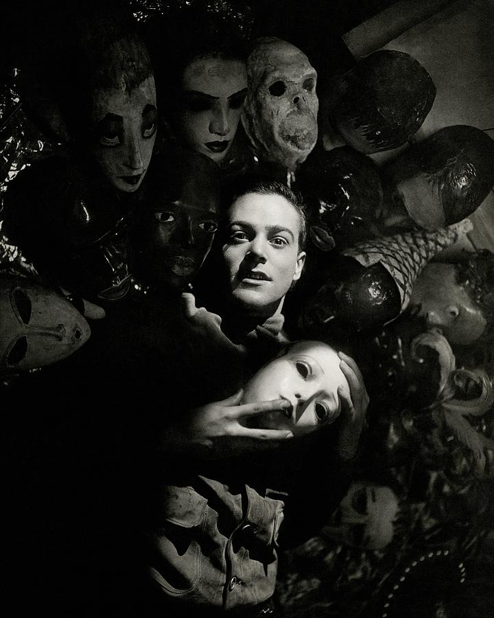 Artist Oliver Messel Surrounded By Various Masks Photograph by George Hoyningen-Huene