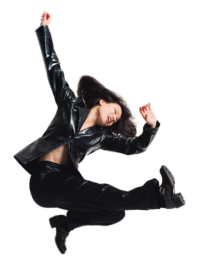 Asain Woman In Black Leather Pants And Jacket Jumping And Kicking Legs Forward With Arms Swinging Upward Photograph by Photodisc