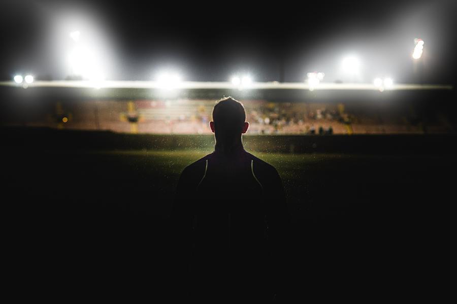 Athlete walking towards stadium silhouette Photograph by Wilpunt