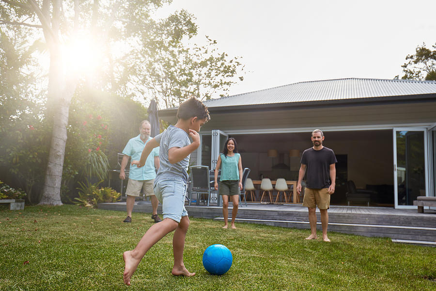 Australian family playing in the back yard garden Photograph by Xavierarnau