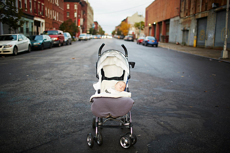 Baby boy asleep in push chair in middle of street Photograph by Cultura/JPM