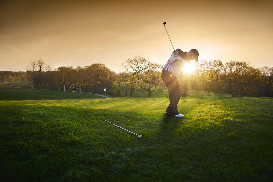 Backlit Golf Course With Golfer Chipping Onto Green Photograph by Sturti