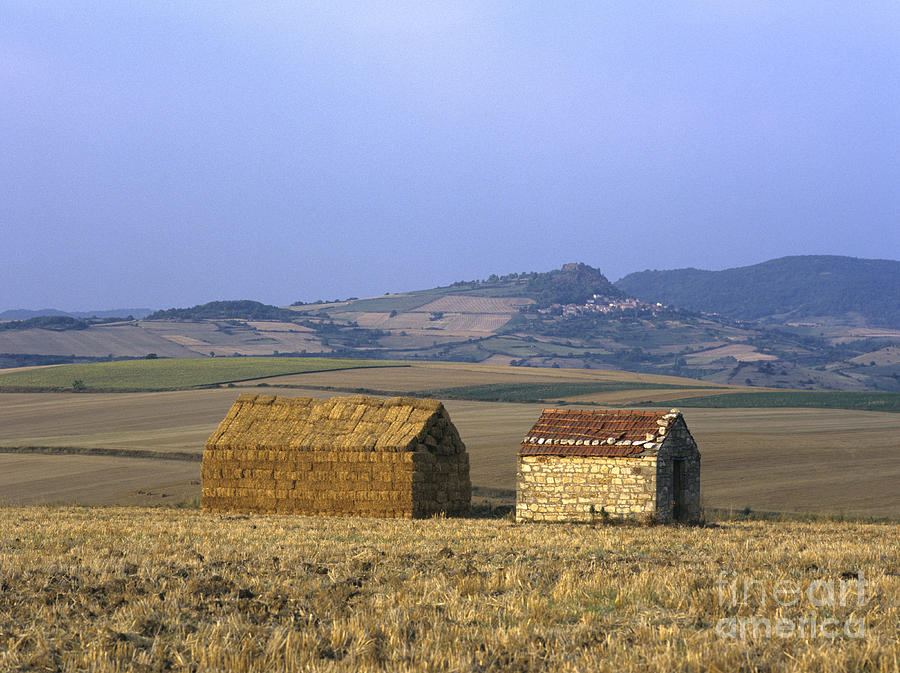 Bales Of Straw Stacked In The Shape Of A House Next To A Little Stone House. Limagne. Auvergne. Fran Photograph by Bernard Jaubert