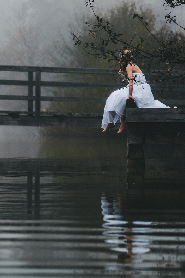 Austria Photograph - Barefoot Bride In White Wedding Dress Sitting On A Jetty At A La by Leander Nardin