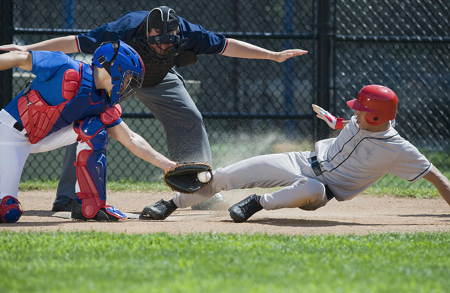 Baseball player sliding into home plate Photograph by Tetra Images