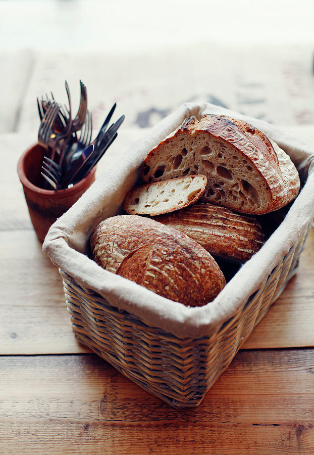 Basket Of Artisan Bread On Wooden Table Photograph by Jake Curtis