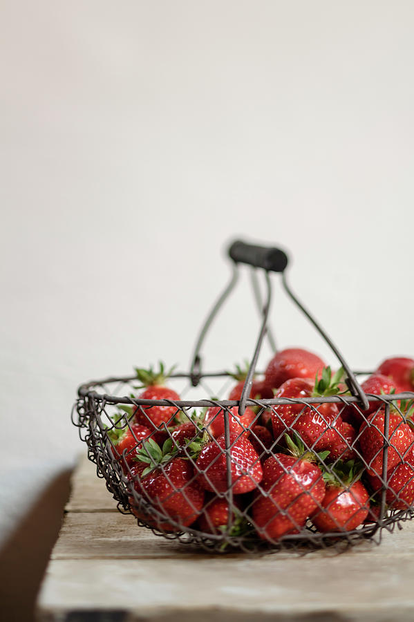 Basket Of Strawberries On Wooden Table Photograph by Westend61