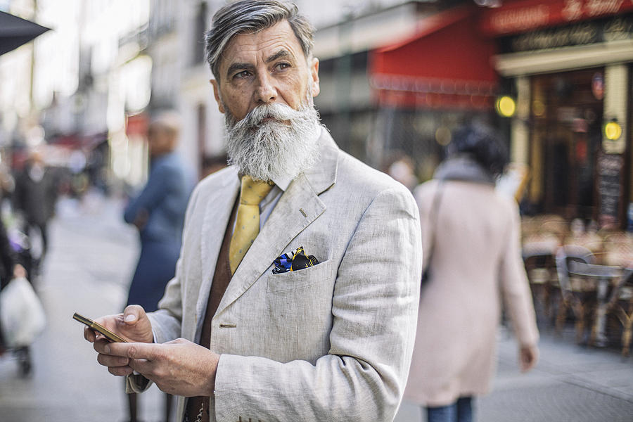 Bearded mature man texting at the street Photograph by Xavierarnau