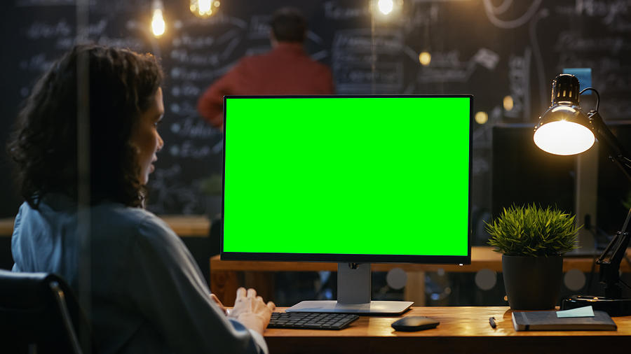Beautiful Female Office Employee At Her Desktop Works On A Mock-up Green  Screen Personal Computer  Over The Shoulder Footage  Her Colleague Works In