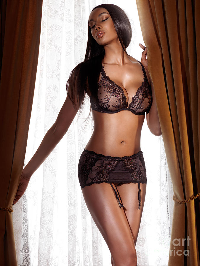 beautiful sexy black woman in lingerie standing at the window