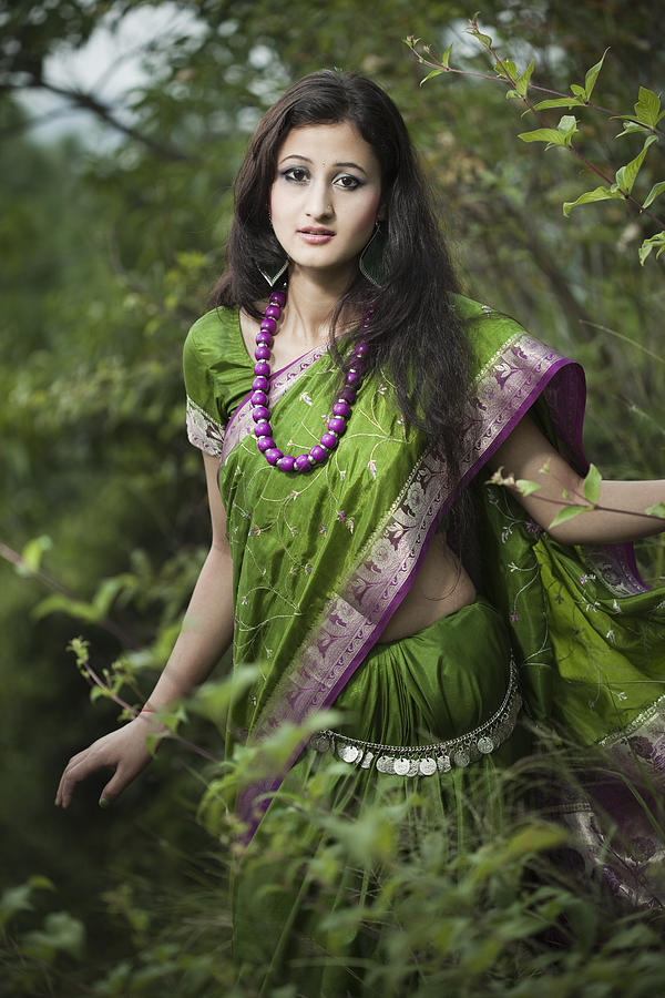 Beautiful young woman in green sari between nature. Photograph by Gawrav