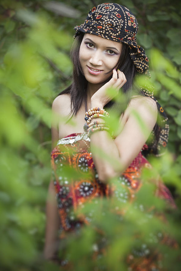 Beautiful young woman in nature behind foliage. Photograph by Gawrav