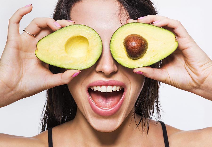 Beauty model holding avocado halves over her eyes Photograph by Dimitri Otis