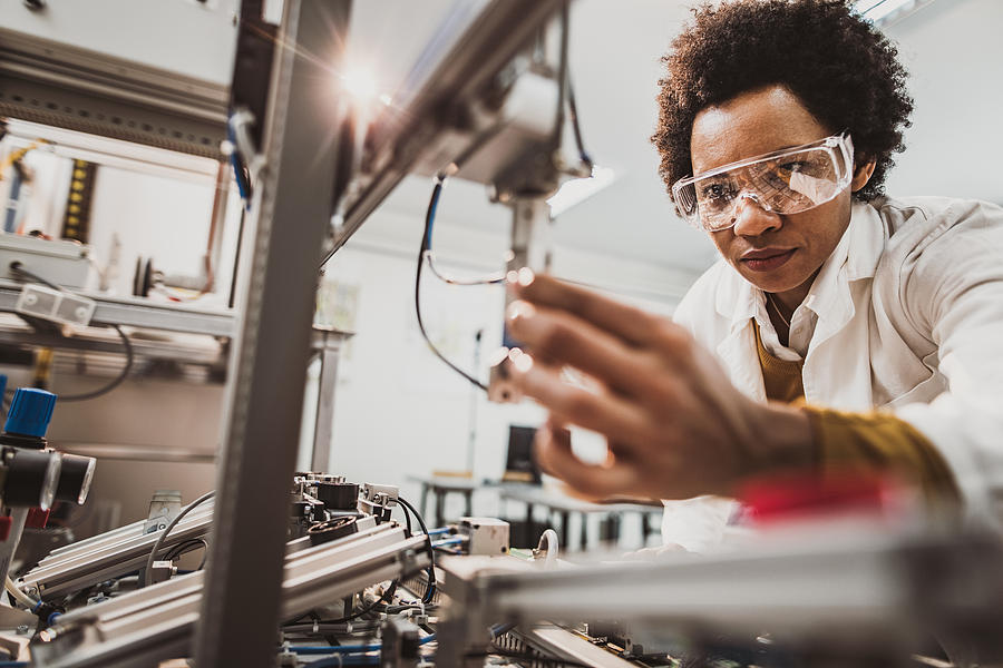 Black female engineer working on industrial machine in a laboratory. Photograph by Skynesher